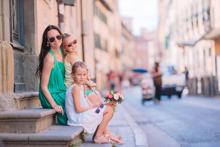 Mother with little cute daughters eating ice-cream outdoor Stock Photo