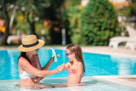 Young mother applying sun cream to daughter nose in the pool. The concept of protection from ultraviolet radiation Zdjęcie Seryjne