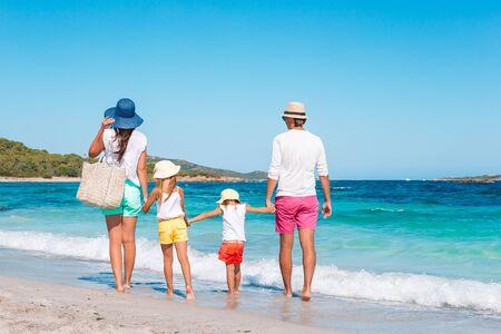 Glückliche schöne Familie am weißen Strand. Rückansicht.