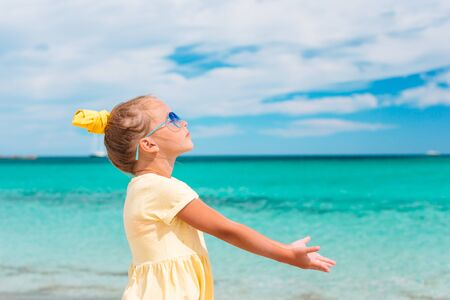 Cute little girl in sunglasses at beach during vacation enjoying vacaion