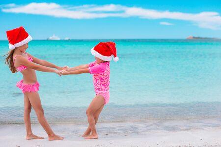 Kleine entzückende Mädchen in Weihnachtsmützen während des Strandurlaubs haben Spaß zusammen Standard-Bild