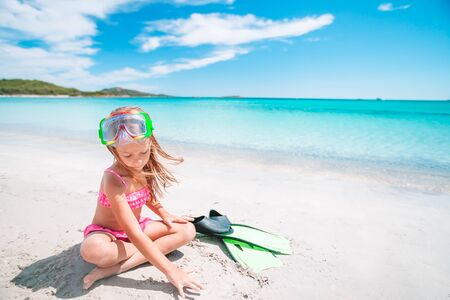 Little girl on the sand with flippers and goggles for snorkling on the beach