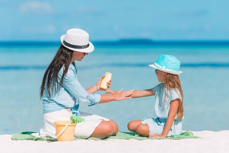 Mother applying sun cream to daughter hand. Sun protection Stock Photo