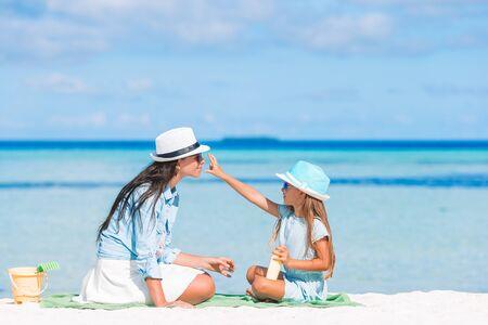 Kleines Kind, das am Strand Sonnencreme auf die Nase der Mutter aufträgt. Das Konzept des Schutzes vor ultravioletter Strahlung
