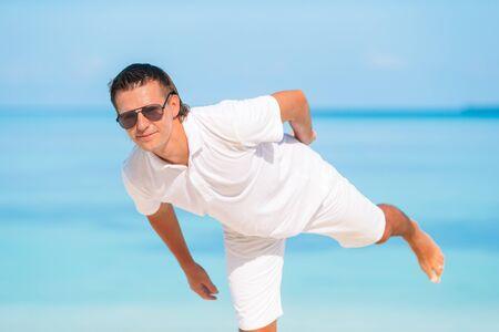 Junger Mann am Strand, der Spaß hat