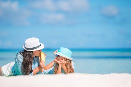 어머니는 딸의 손에 썬크림을 바르고 있습니다. 태양 보호
