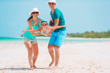 Young family on white beach during summer vacation Stock Photo - 137230729