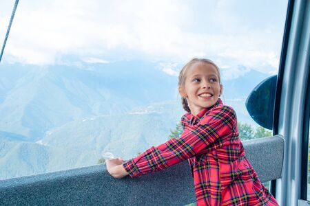 Entzückendes kleines Mädchen in der Kabine der Seilbahn