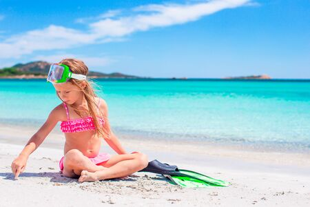 Little girl with flippers and goggles for snorkling on the beach Stock fotó