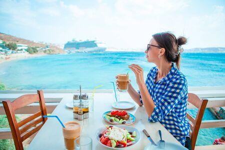 Mujer bebiendo café caliente en la terraza del hotel de lujo con vistas al mar en el restaurante del resort. Foto de archivo
