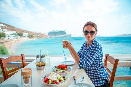 Frau, die heißen Kaffee auf Luxus-Hotelterrasse mit Meerblick am Resort-Restaurant trinkt.