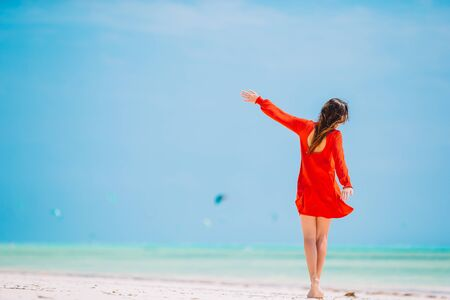 Young beautiful woman having fun on tropical seashore. Happy girl background the blue sky and turquoise water in the sea on caribbean island
