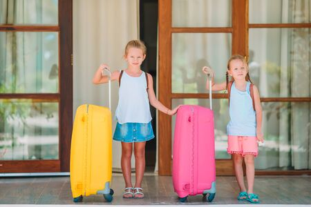 Kids with two luggages ready to travel