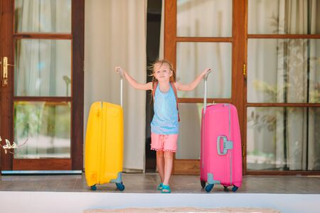 Adorable little girl with luggages ready for traveling Stock Photo