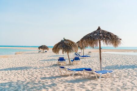 Idyllic tropical beach with white sand, turquoise ocean water and sunbeds and umbrellas