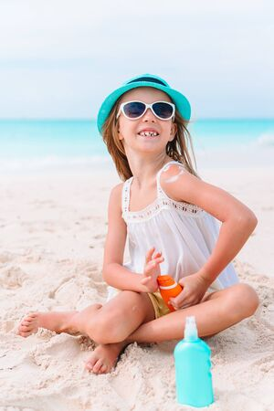 Little adorable girl with bottle of sun cream sitting at tropical beach 版權商用圖片