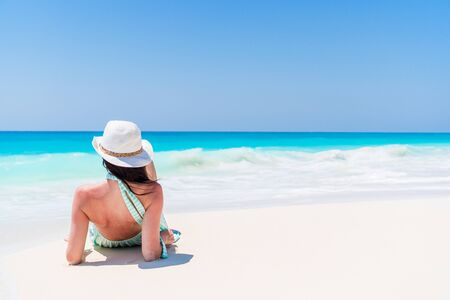 Young beautiful woman relaxing on the beach. Back view of happy girl on the seashore