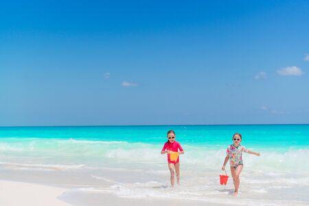 Petites filles sur la plage tropicale s'amusant à la course au bord de la mer