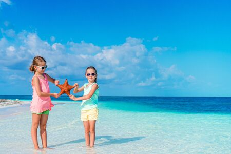 Adorable little girls with starfish on the beach in natural reserve