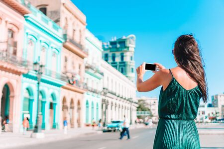 Woman on the street in Havana, Cuba. Young woman traveler taking foto of famous sight