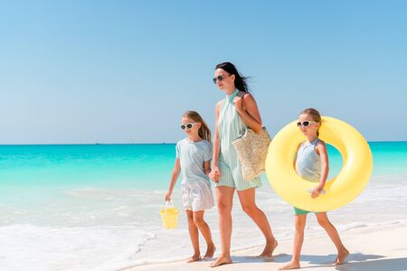 Adorable little girls and young mother on white beach. Family on the beach ready to swim Foto de archivo