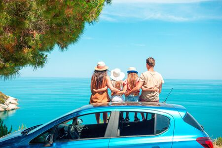Family traveling by car, sitting on the roof and looking at the sea
