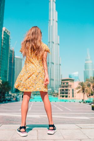 Back view of little girl walking in Dubai with skyscrapers in the background.
