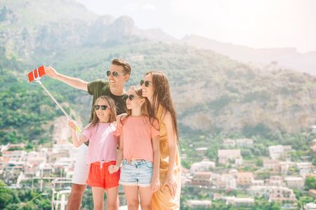 Parents and kids taking selfie photo background Positano town in Itali on Amalfi coast
