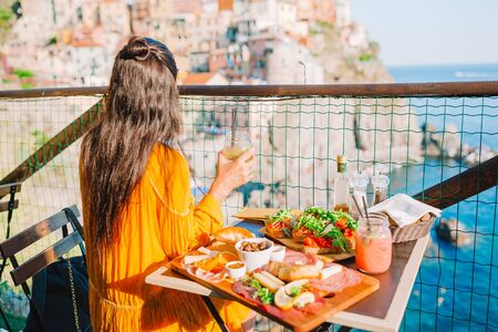 Beautiful woman on breakfast at outdoor cafe with amazing view in Cinque Terre Standard-Bild