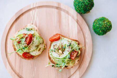 Italian bruschetta with cherry tomatoes, avocado, basil and parmesan cheese on the wooden desk 版權商用圖片