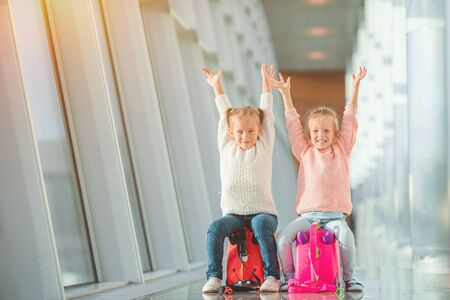 Adorable little girls in airport with her luggage waiting for boarding