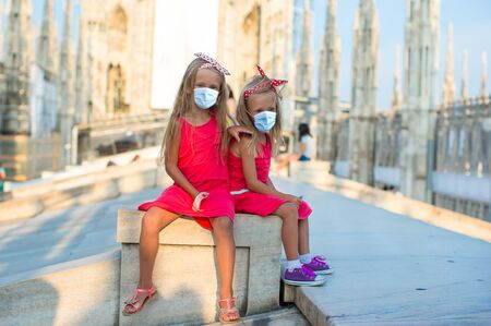 Adorable little girls in masks on the rooftop of Duomo, Milan, Italy