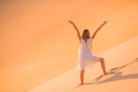 Beautiful girl in white dress on vacation in dunes in beautiful desert