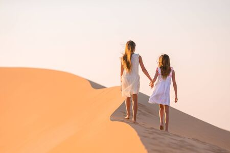 Little beautiful girls at dunes in most big sand desert in the world at sunset