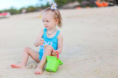 Little adorable girl at tropical beach making sand castle Reklamní fotografie
