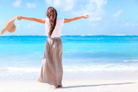 Young happy woman on white beach walking. Young beautiful woman having fun on tropical seashore.