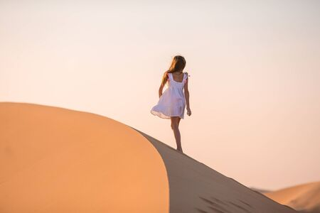 Girl among dunes in desert in United Arab Emirates Фото со стока