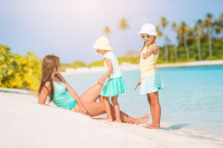 Mother and little girls on vacation on the beach