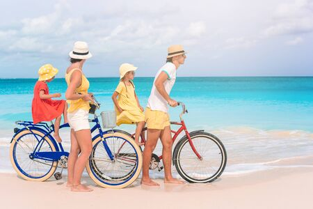 Family with a bike on tropical beach