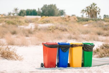 Bright plastic containers for garbage sorting on the beach. Red, yellow, blue and green containers for glass, plastic, wastes and paper on the sand beach on the seaside. Ecology and recycling concept