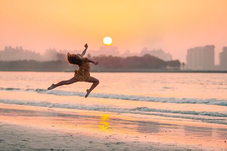 Adorable happy little girl on the beach at sunset