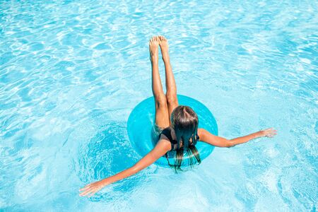 Little happy girl in outdoor swimming pool having fun with rubber ring Archivio Fotografico