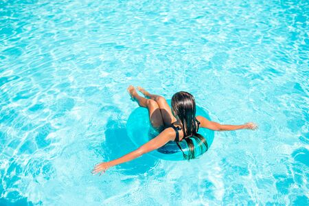 Little happy girl in outdoor swimming pool having fun with rubber ring