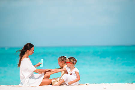 Young mother applying sun cream to daughter nose on the beach. Sun protection Banque d'images
