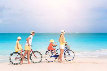 Family of four riding bicycles on the beach