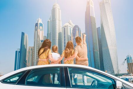 Family summer vacation. Family of four on car vacation on background of skyscrapers in Dubai