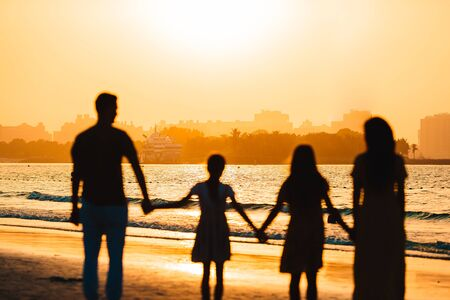 Silhouette of family on the beach at sunset 版權商用圖片 - 147847387