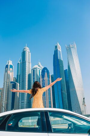 Woman sitting on the car on background of skyscrapers in Dubai
