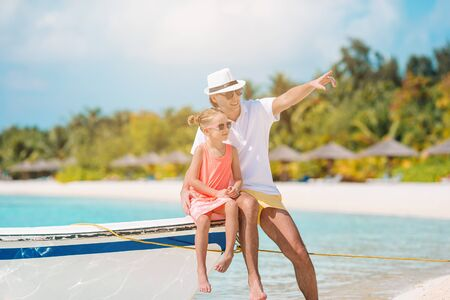 Happy father and his adorable little daughter on the beach on the boat