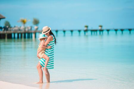 Family of mom and little girl have fun on the beach